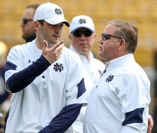 CHAD WEAVER | THE GOSHEN NEWS<br /> Former Notre Dame quarterback and first-year quarterbacks coach Tom Rees talks with head coach Brian Kelly prior to the start of Saturday's Blue-Gold game at Notre Dame Stadium.