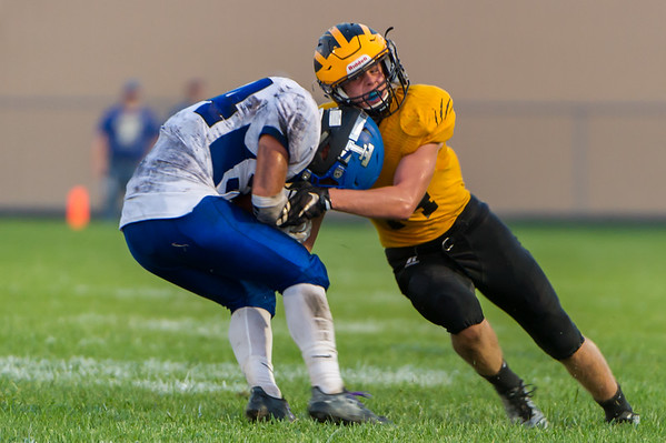 Panthers linebacker Miles Von Tobel (14) wraps up Trojan running back Max Slusser (34) for a stop in the first half as Pioneer took on Triton at The Pit on Thursday evening. Fran Ruchalski | Pharos-Tribune