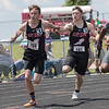 Nicholas Eckels receives the handoff from Chandler Breeden in the first leg of the boys 4x100 relay