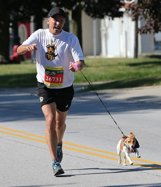 AARON JOSEFCZYK / GAZETTE Joe Pavlic of Medina runs with his dog Ginger during the 10-kilometer race at the Medina Twin Sizzler event.