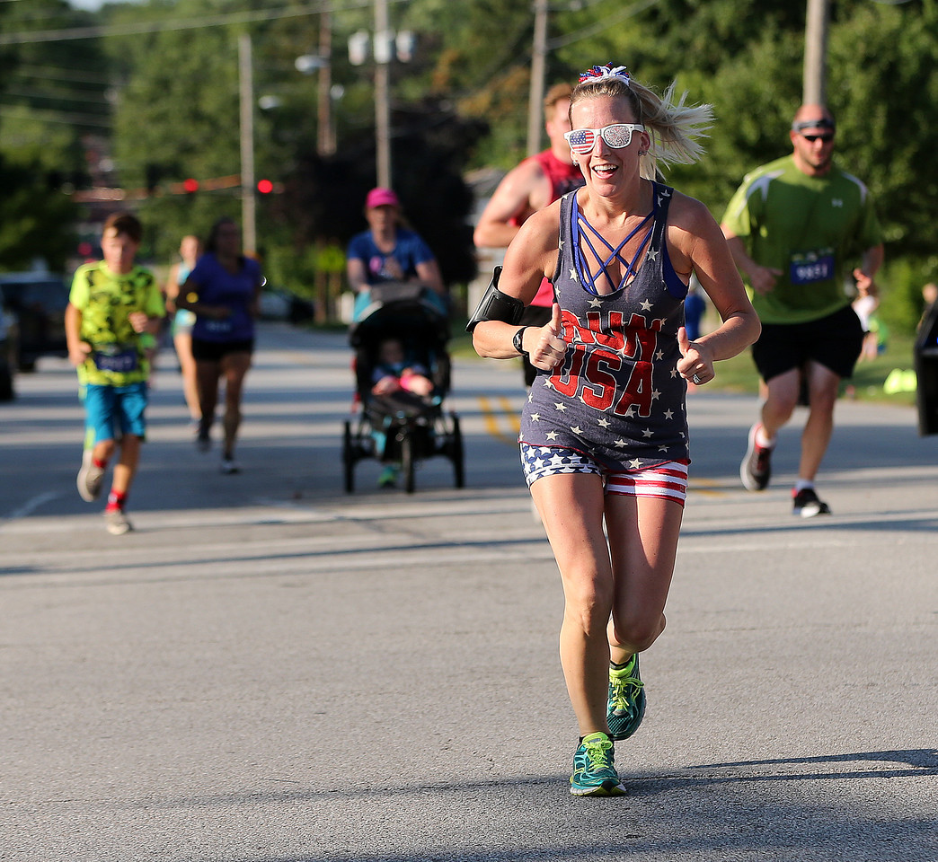 AARON JOSEFCZYK / GAZETTE Nicole Janik of Medina gives a thumbs-up sign as she runs to the finish of the 5-kilometer race at the Medina Twin Sizzler event held Tuesday.