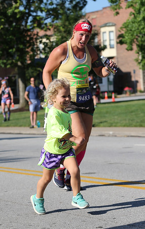 AARON JOSEFCZYK / GAZETTE Former Medina resident Becki Falatach runs with her daughter Rori during a kids fun run held Tuesday as part of the Medina Twin Sizzler event.