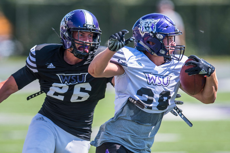 Running back Josh Davis (28) outruns defender Justus Brown (26) during the football scrimmage on Thursday August 17, 2017. At Stewart Stadium at the campus of Weber State in Ogden.