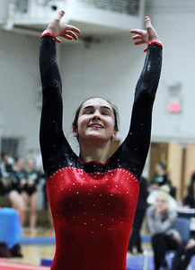 ANNA NORRIS/CHRONICLE Elyria's Sarah Scneider smiles after she sticks her landing of her final tumbling pass of her floor routine in the Northeast Ohio sectional gymnastics meet Sunday afternoon at West Geauga High School.