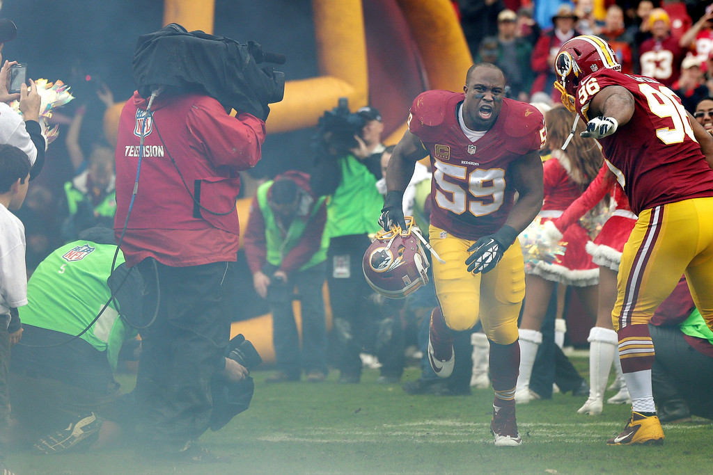 . Washington Redskins inside linebacker London Fletcher runs onto the field after his introduction before an NFL football game against the Dallas Cowboys in Landover, Md., Sunday, Dec. 22, 2013. (AP Photo/Mark Tenally)