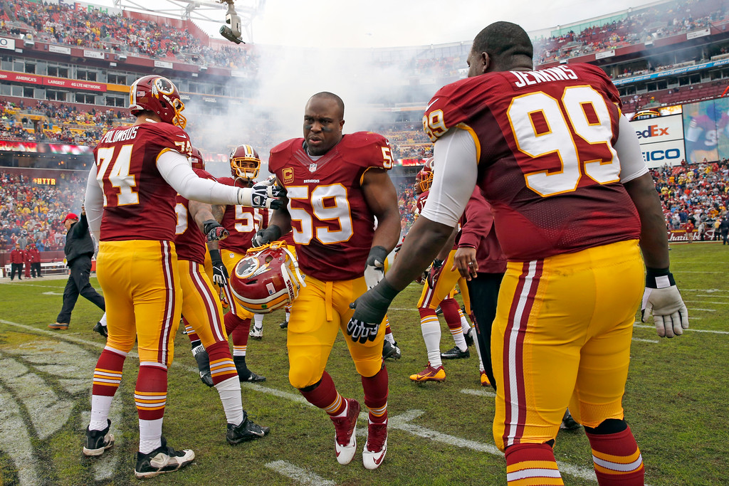 . Washington Redskins inside linebacker London Fletcher (59) runs past his fellow players as he introduced before an NFL football game against the Dallas Cowboys in Landover, Md., Sunday, Dec. 22, 2013. (AP Photo/Alex Brandon)