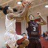 Jwan Evans drives in for the layup drawing a fowl from Colin Williams