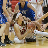 Sage Fox grabs on to a loose ball as is surrounded by the Madison defense