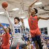 Robert Smith sails in for a layup between Patrick Mears (2) and Je'Hova Warren (4)