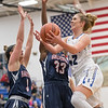Casey Irvine drives in for a layup against Atilia Thomas