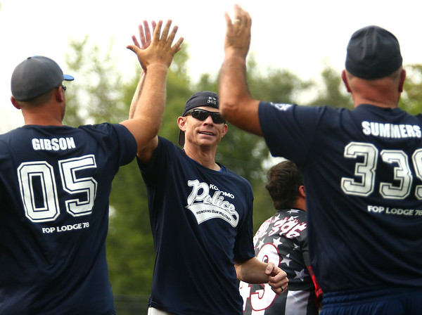 KPD's Chad VanCamp is congratulated by teammates Nate Gibson and Kevin Summers after VanCamp crosses home plate in the seventh inning, scoring the game winning run. Kokomo Police Department defeated the Kokomo Fire Department 8-7 in the Military Foundation charity softball game on Saturday, August 18, 2018.<br /> Kelly Lafferty Gerber | Kokomo Tribune