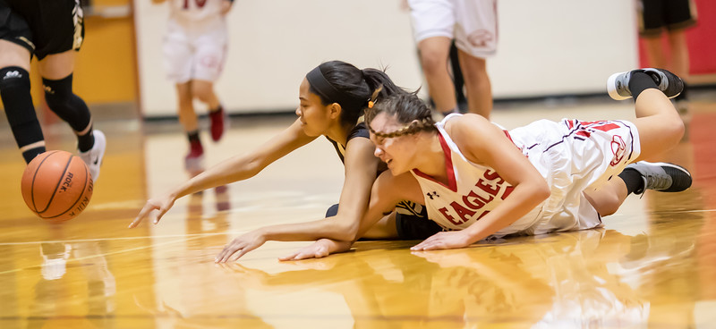 The ball squeezes out as Amaya Lucas and Naomi Gibson dives in on it.