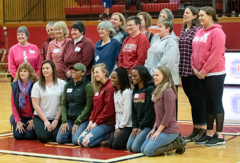 Basketball Alumni gather at center court for recognition