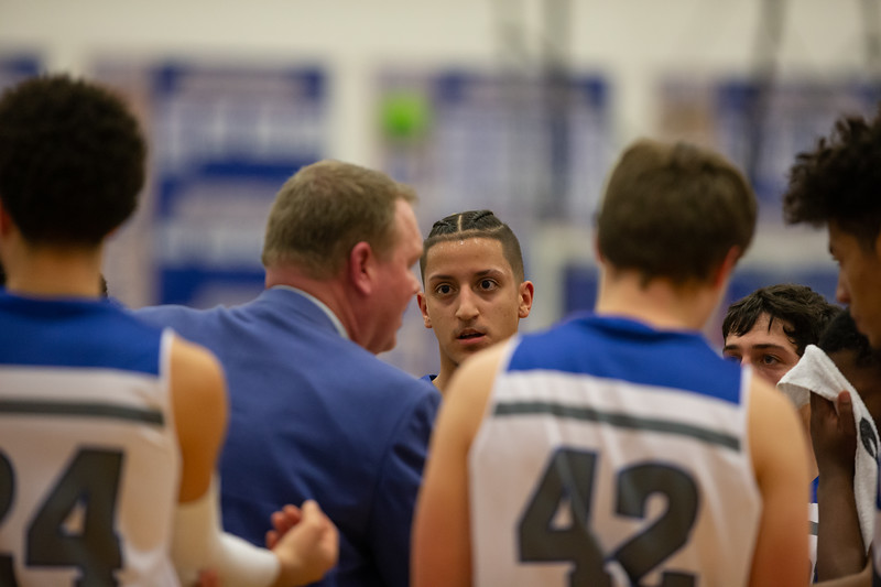 Angel Pacheco-Ortiz listens as Coach Edwards tries to rally his team during a timeout