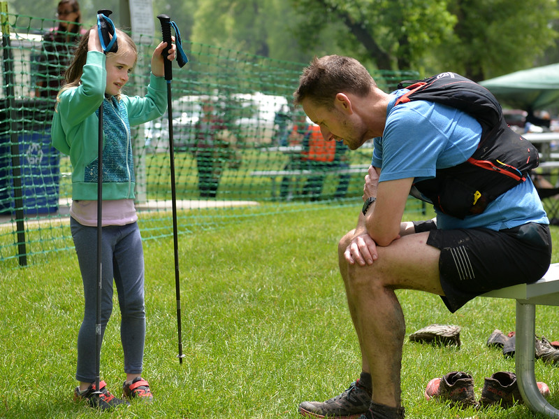 Justin Sheely | The Sheridan Press<br /> 100-miler Philip Vondra of Brooklyn, New York, rests as his daughter Emily Vondra plays with his poles during the Bighorn Mountain Wild and Scenic Trail Run at Scott Park in Dayton Saturday, June 16, 2018.