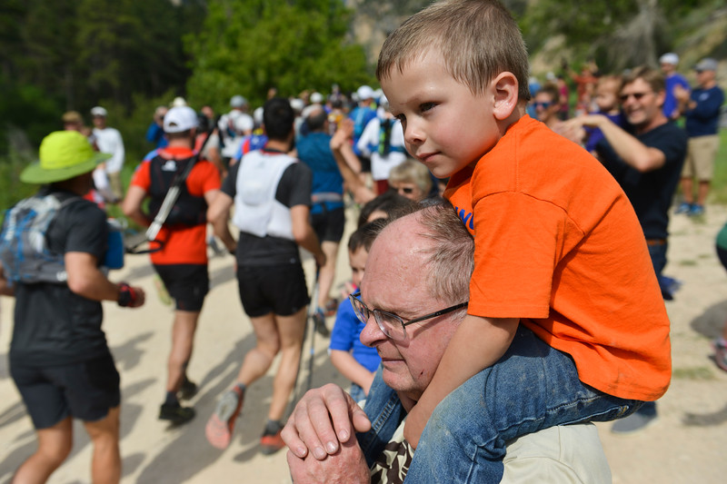 Justin Sheely | The Sheridan Press<br /> Bart Spencer holds his grandson Hoyt Jasso, 4, as he looks for his father in the 100-mile race during the Bighorn Mountain Wild and Scenic Trail Run at the Amsden Creek fishing area near Dayton Friday, June 15, 2018.