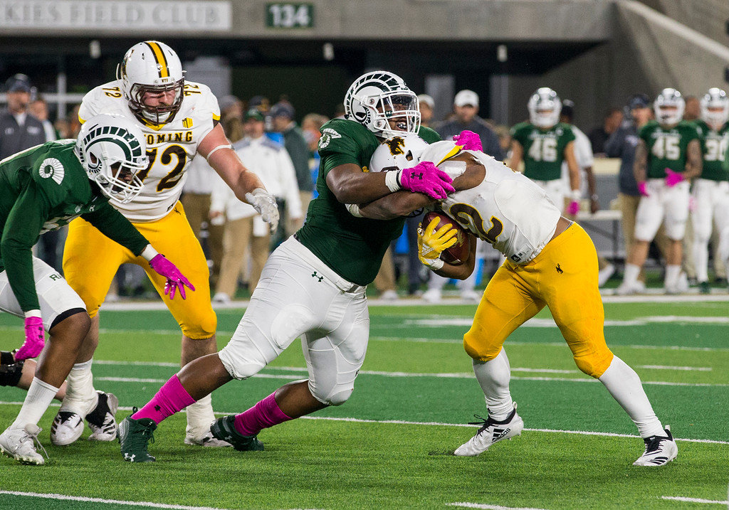 . Colorado State defensive lineman Ellison Hubbard (98) gets a grip on Wyoming running back Nico Evans (22) Friday evening Oct., 26 2018 at Canvas Stadium in Fort Collins. (Michael Brian/For the Reporter-Herald)