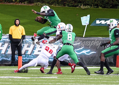 Marshall's Tyler King leaps over FAU's Chris Tooley on Saturday.  MARTY CONLEY/ FOR THE DAILY INDEPENDENT