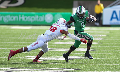 Marcel Williams of Marshall stiff arms Florida Atlantic's Silver Saunders on Saturday.  MARTY CONLEY/ FOR THE DAILY INDEPENDENT