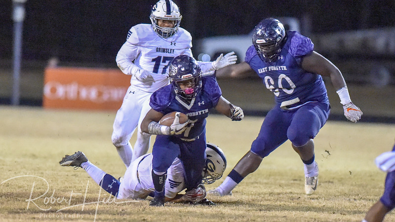East Forsyth's Robbin Smith (7) is tackled by Grimsley's Born Lesane (2) at Fred E. Lewis Stadium in Kernersville, North Carolina on Friday, November 30, 2018. (Photo by Robert Hill)
