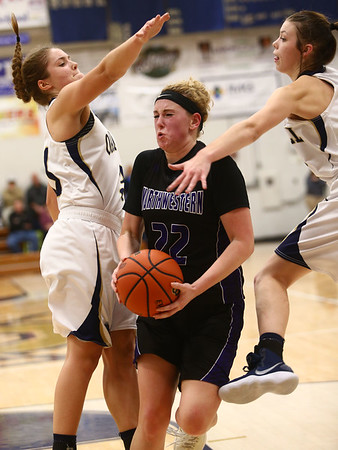 1-10-18<br /> Northwestern vs Oak Hill girls basketball<br /> NW's Taylor Boruff breaks through two Oak Hill defenders as she heads to the basket.<br /> Kelly Lafferty Gerber | Kokomo Tribune
