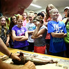 10-year-old Kira Hood peeks from behind her hand as she watches Jeff Fager fillet a fish in the Kids Fishing Clinic fish cleaning class on Thursday, July 26, 2018.<br /> Kelly Lafferty Gerber | Kokomo Tribune