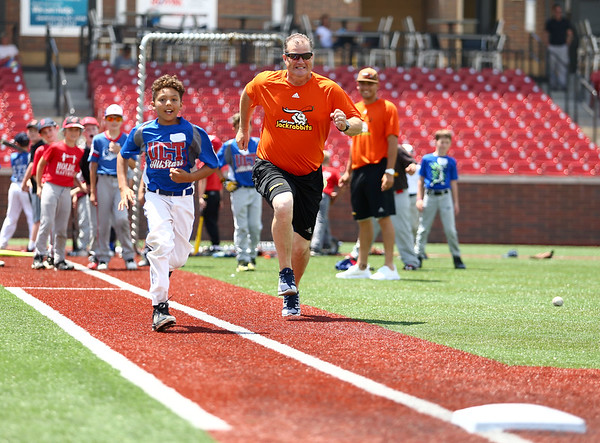 9-year-old Jaiden McNulty races and beats Jackrabbits coach Gary McClure during a sprint to first base at the Jackrabbits kids baseball camp on Wednesday, June 27, 2018.<br /> Kelly Lafferty Gerber | Kokomo Tribune