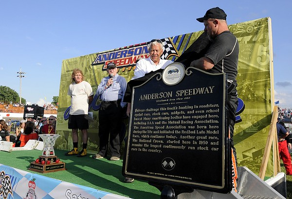 Don Knight   The Herald Bulletin<br /> Rick Dawson and Eric Gordon unviel a historical marker for the Anderson Speedway during prerace activities for the Little 500 on Saturday.
