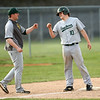 5-1-18<br /> Taylor vs Eastern baseball<br /> Eastern's Logan Smith fist bumps with his coach Nick Sale after hitting a triple in the seventh inning.<br /> Kelly Lafferty Gerber | Kokomo Tribune