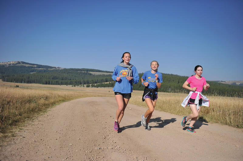 Bud Denega | The Sheridan Press<br /> Josie Fettig, left, Katie Turpin, center, and Kate Moran run along Forest Service Road 231 during the Sheridan High School cross-country team's annual mountain camp Thursday, August 16, 2018.