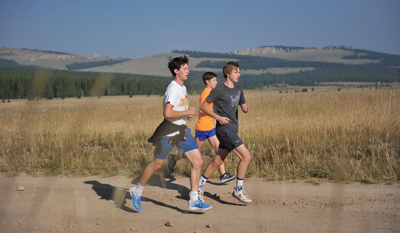 Bud Denega | The Sheridan Press<br /> Alex Garber, left, Garett Avery, middle and David Standish warm-up during the Sheridan High School cross-country mountain camp at 4-H Campground near Burgess Junction Thursday, August 16, 2018.