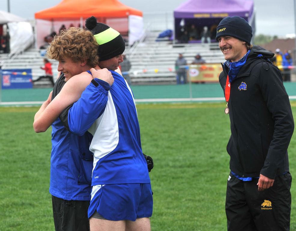 Bud Denega | The Sheridan Press<br /> Sheridan's Brian Gonda hugs assistant track coach Art Baures following the 1,600-meter run during the state track and field meet at Kelly Walsh High School Saturday, May, 19, 2018.