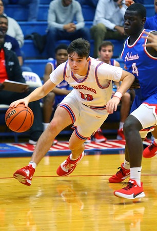 Bobby Wannell driving around Lynn King in Saturday afternoon action between the Kokomo Wildcats and South Bend Adams Eagles on December 28, 2019.<br /> Tim Bath | Kokomo Tribune