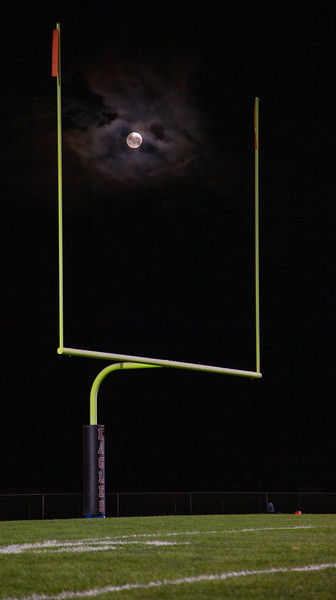 A full moon on Friday the 13th raises through the uprights