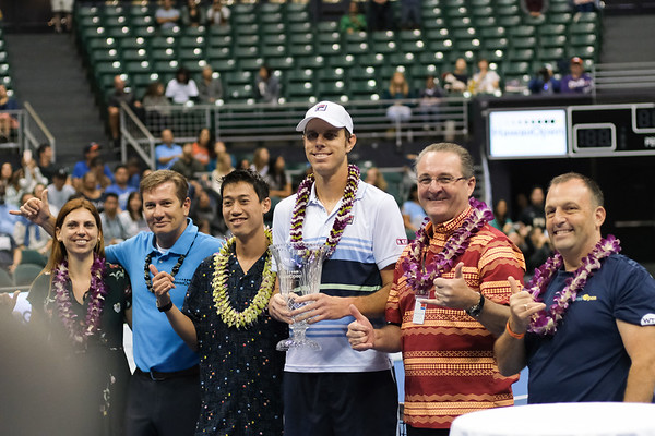 Sam Querrey holds his men's championship trophy alongside Kei Nishikori at the 2019 Hawaii Open at the Stan Sheriff Center on December 28, 2019 in Honolulu, Hawaii.