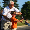 "7-18-19<br /> Tim Buckley shades the eyes of his grandson, 6-year-old Gabe Yentes so Yentes can see the target during casting practice at the Jim ""Moose"" Carden Kids Fishing Clinic at Kokomo High School.<br /> Kelly Lafferty Gerber 