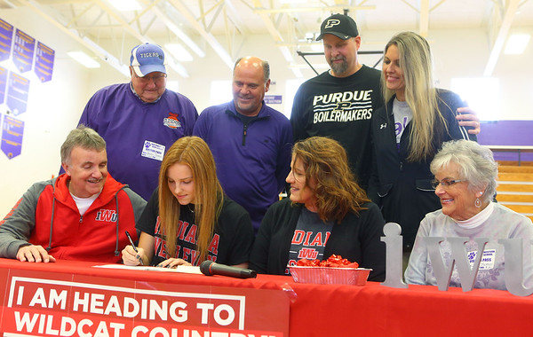 11-13-19<br /> Surrounded by family and coaches, Klair Merrell, center, signs to play basketball at Indiana Wesleyan.<br /> Kelly Lafferty Gerber   Kokomo Tribune
