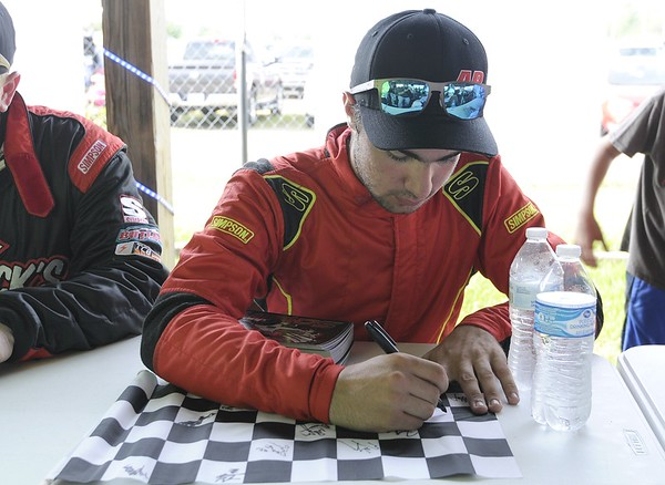 Don Knight   The Herald Bulletin<br /> Little 500 rookie Joey Schmidt signs a checkered flag for a fan before the start of the little 500 on Saturday.