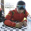 Don Knight | The Herald Bulletin<br /> Little 500 rookie Joey Schmidt signs a checkered flag for a fan before the start of the little 500 on Saturday.