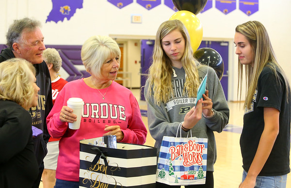McKenna Layden shows a card to her grandparents Dave and Joyce Wise, as McKenna's sister, Madison looks on after Madison officially signed with Purdue on Nov. 13.<br /> Kelly Lafferty Gerber | Kokomo Tribune