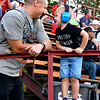 Tripp Bagienski, 3, stands on the railing so his can talk to his dad, Tony Bagienski, of Fishers, face-to-face before the start of the Little 500.