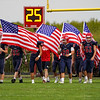 Lewis Cass Kings player walk out not he field with flags to honor 13 service members who were killed and those injured last week in Afghanistan before the game at Owens Memorial Field in Walton on Friday, Sept. 3, 2021.
