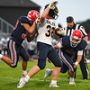 Lewis Cass Kings middle linebacker Elijah Martin (20) and Lewis Cass Kings linebacker Haden McClain (30) combine to tackle Delta Eagles' Dylan Manor (32) during the first half of a game between the Lewis Cass Kings and Delta Eagles at Owens Memorial Field in Walton on Friday, Sept. 3, 2021.