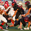 Logansport Berries defensive players go to tackle Richmond Red Devils running back Demarco Owens (11) during the first half of a game at Logansport Memorial Hospital Stadium in Logansport on Friday, Sept. 24, 2021.