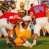 Pioneer Panthers defensive lineman Oscar Solano (77) and another player tackle a Caston Comets player during a game at Caston High School in Fulton on Friday, Sept. 10, 2021.