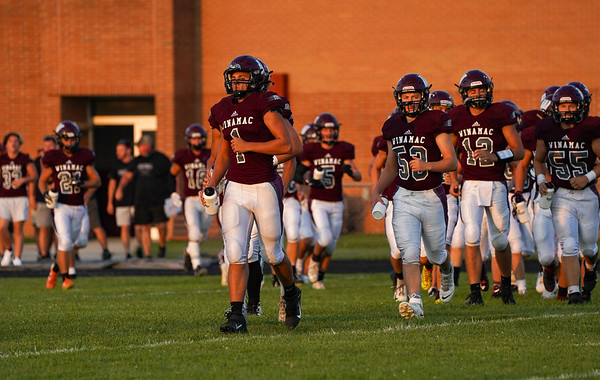 Winamac Warriors players run on the field before an HNAC game between the Winamac Warriors and Pioneer Panthers at Winamac High School on Friday, Aug. 27, 2021.