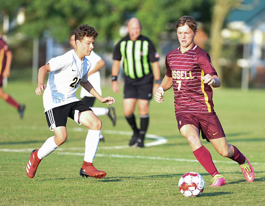 Blake Hern of Russell dribbles as Fleming County's Wade Skaggs defends on Thursday evening at Russell.  MARTY CONLEY/ FOR THE DAILY INDEPENDENT