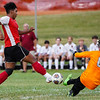 Logansport Berries forward Humberto Baez (7) tries to get the ball past McCutcheon Mavericks goalkeeper Gabe Puentes (0) during the first half of an NCC game between the Logansport Berries and McCutcheon Mavericks at Logansport High School on Thursday, Aug. 26, 2021.