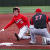 Twin Lakes Indians outfielder Ethan Bowsman (18) slides to third base as Logansport Berries third baseman Mike Meadows (27) applies a tag during the sixth inning of a game between the Logansport Berries and Twin Lakes Indians on Saturday, April 10, 2021 in Logansport.