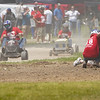 People work on a mower as racers continue on during the Twelve Mile 500's Briggs Race at Plank Hill Park in Twelve Mile on Sunday, July 4, 2021.